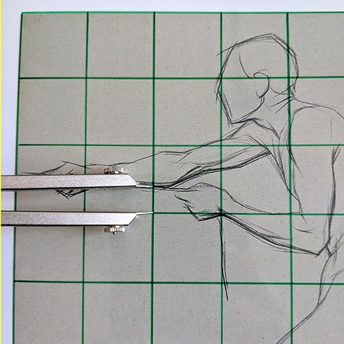 Calipers on top of a drawing with a grid.