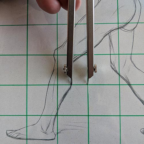 Calipers measuring a drawing.