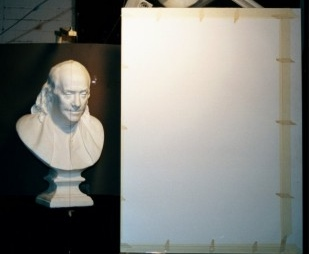 A photograph of a plaster cast placed next to a drawing board.