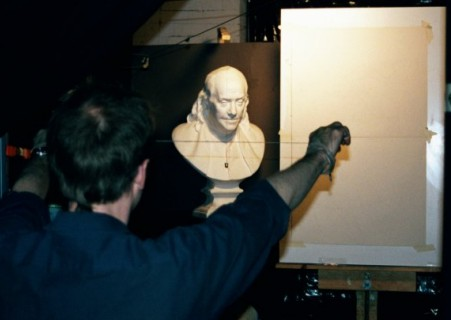 A photograph of an artist demonstrating using the sight size method.