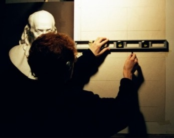 A photograph of an artist using a ruler to draw lines and using the sight size method.